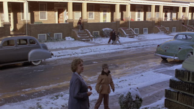 medium angle of sides street of residential area. see woman and child walk out sidewalk, could be principal actors. snow on ground, classic cars pass by  on street. - calle principal calle video stock e b–roll