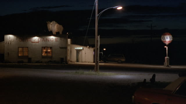 vídeos de stock, filmes e b-roll de medium angle of lone gas pump on right next to dance studio with cut out buffalo logo on roof. dance studio is one story, street lamp in center. dark shot. - dance studio