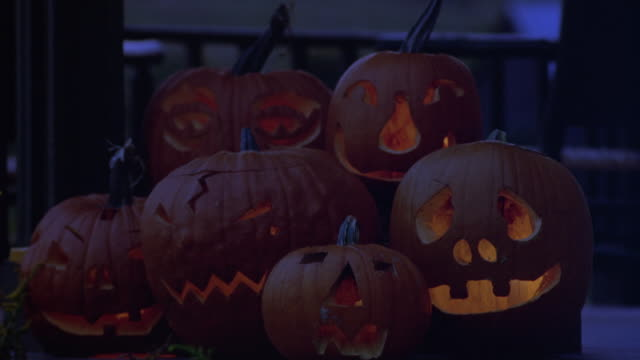 MEDIUM ANGLE OF TWO ROWS OF JACK-O-LANTERNS CARVED IN VARIOUS EXPRESSIONS ON PORCH WITH CANDLE LIGHT FLICKERING INSIDE. HALLOWEEN.