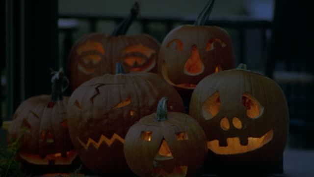 medium angle of two rows of jack-o-lanterns carved in various expressions on porch with candle light flickering inside. halloween. - halloween stock-videos und b-roll-filmmaterial