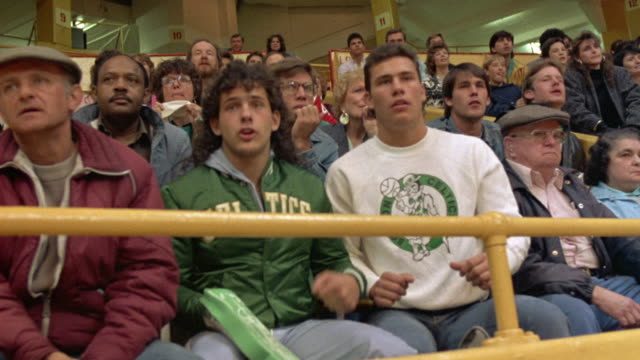 MEDIUM ANGLE OF FANS SITTING IN BOSTON GARDEN WATCHING CELTIC BASKETBALL GAME. SEE FANS WITH PENSIVE FACES. SEE FANS URGING ON THEIR TEAM. SEE CELTIC SHIRTS, JACKETS, AND FOAM HAND.