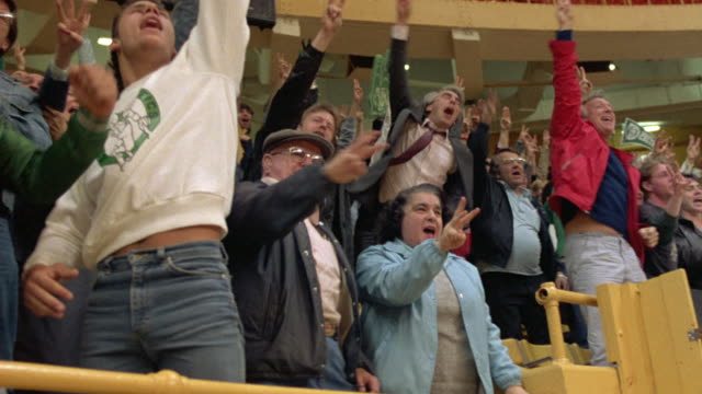 MEDIUM ANGLE OF FANS AT BOSTON GARDEN WATCHING CELTIC BASKETBALL GAME. SEE FANS STANDING AND CELEBRATING. SEE FANS SIT DOWN. SEE CELTIC SHIRTS, JACKETS, AND FOAM HAND.