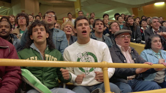 MEDIUM ANGLE OF FANS SITTING IN BOSTON GARDEN WATCHING CELTIC BASKETBALL GAME. SEE FANS WITH PENSIVE FACES.
