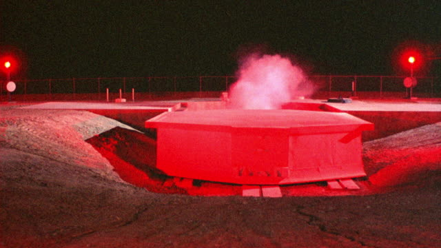 medium angle of missile base silo and cover bathed in red light. see steam or smoke emit from open silo cover. see red flashing lights around silo and cover. - silo stock videos & royalty-free footage