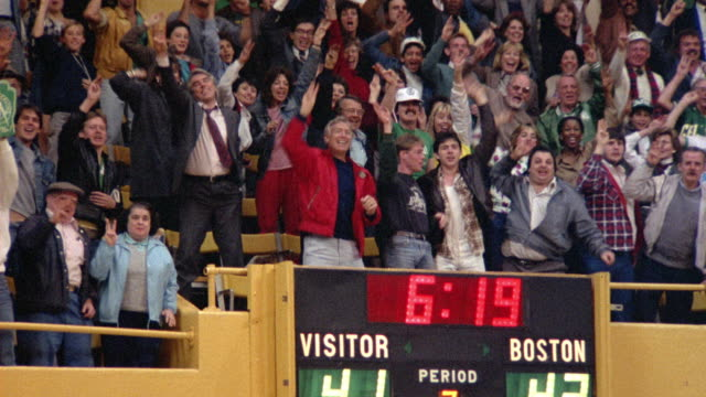 MEDIUM ANGLE OF SPECTATORS AT A BOSTON CELTICS GAME. SEE FANS BURST INTO APPLAUSE AND STAND UP. SEE FANS CELEBRATE WITH THREE FINGER SALUTE.