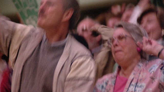 CLOSE ANGLE OF TWO SPECTATORS AT A BASKETBALL GAME. SEE SPECTATORS AND FANS BEHIND THEM WATCH UNSEEN ACTION OF GAME, BURST INTO APPLAUSE AND STAND UP.