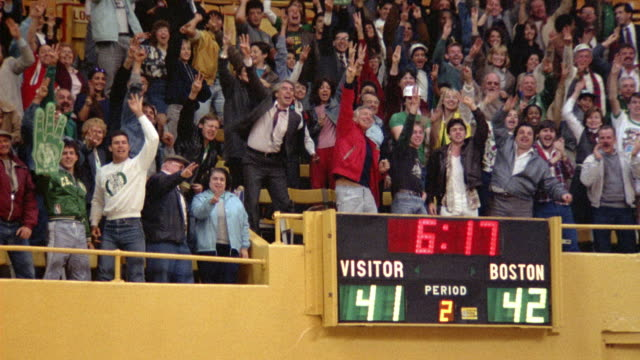 MEDIUM ANGLE OF SPECTATORS AND SCOREBOARD AT A BOSTON CELTICS GAME. SEE FANS BURST INTO APPLAUSE AND STAND UP.