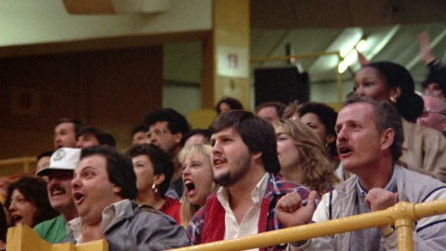 MEDIUM ANGLE OF SPECTATORS AT A BASKETBALL GAME. SEE FANS WATCH UNSEEN ACTION OF GAME, BURST INTO APPLAUSE AND STAND UP.