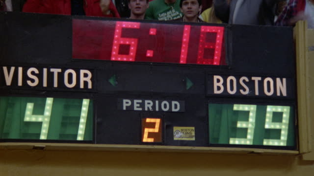 pan up from basketball scoreboard to spectators at a boston celtics game. see fans burst into applause and stand up. - スコアボード点の映像素材/bロール