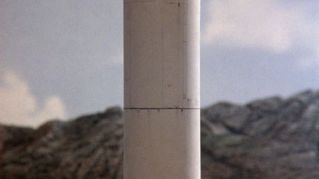 close angle pan up of missile launch. see smoke and sparks emanate from missile engine. see mountains in background. see blue sky with white puffy clouds. could be conventional or nuclear weapon. - lenkflugkörper stock-videos und b-roll-filmmaterial