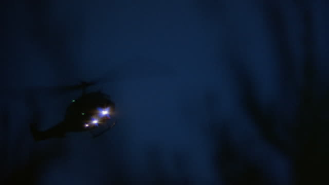 pan left to right of helicopter silhouette flying towards frame right in dusky sky. see search lights and flashing lights on helicopter. see occasional out of focus plant silhouette  in foreground. could be military helicopter. - military helicopter stock videos and b-roll footage