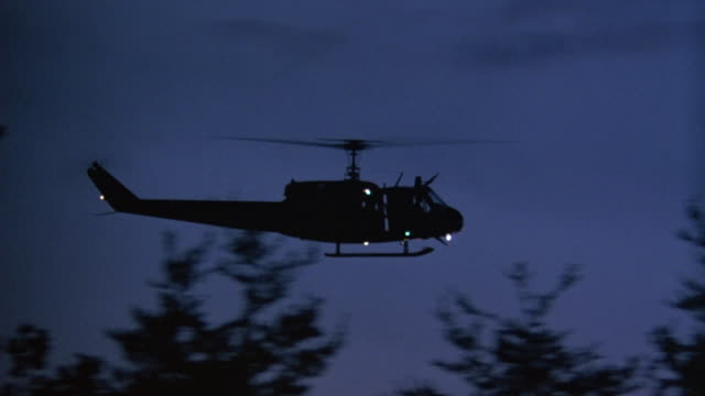 pan left to right of helicopter silhouette flying towards frame right in dusky sky. see helicopter obscured by silhouetted trees in foreground. see search lights and flashing lights on helicopter. could be military helicopter. - suchscheinwerfer stock-videos und b-roll-filmmaterial
