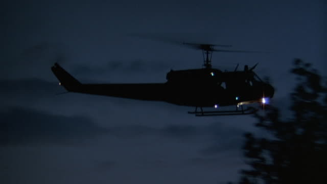pan left to right of helicopter silhouette flying towards frame right in dusky sky. see helicopter obscured by silhouetted trees in foreground. - suchscheinwerfer stock-videos und b-roll-filmmaterial