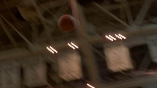 up angle pan right to left from boston celtics championship banners hanging in rafters to basketball flying to basket and going through hoop. see lights on ceiling. - basketball hoop stock videos & royalty-free footage