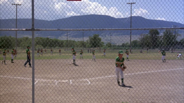 PAN LEFT TO RIGHT MEDIUM ANGLE OF BOYS PRACTICING OR WARMING UP ON A BASEBALL FIELD. POV FROM STANDS BEHIND CHAIN LINK FENCE AT HOME PLATE LOOKING OUT TOWARDS OUTFIELD.
