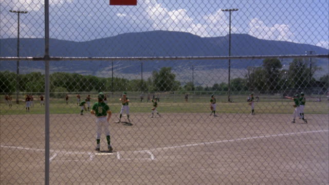 MEDIUM ANGLE OF BOYS PRACTICING OR WARMING UP ON A BASEBALL FIELD. POV FROM STANDS BEHIND CHAIN LINK FENCE AT HOME PLATE LOOKING OUT TOWARDS OUTFIELD.