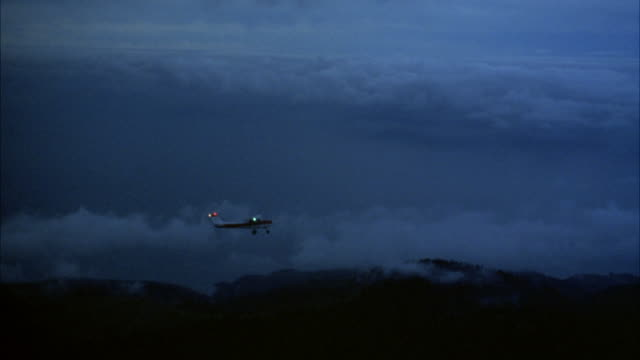 AERIAL SHOT OF SMALL PROPELLER AIRPLANE, POSSIBLY CESSNA, FLYING OVER CLOUD COVER AND MOUNTAIN TOP. SEE LIGHTS ON PLANE FLASH.