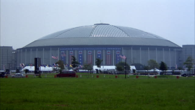 stockvideo's en b-roll-footage met medium angle of houston astrodome. see american and state flags blowing in wind. - 1992