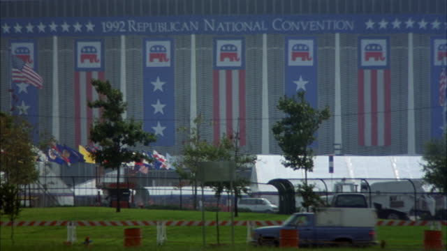 close angle of houston astrodome. see american and state flags blowing in wind. see trees blow in wind. - 1992 stock-videos und b-roll-filmmaterial