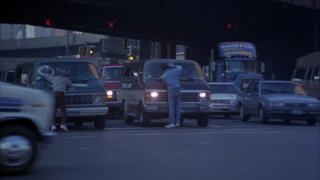 stockvideo's en b-roll-footage met medium angle of new york city street intersection. see pedestrians cross street as possibly homeless men wash windshields of cars stopped at signal. - men