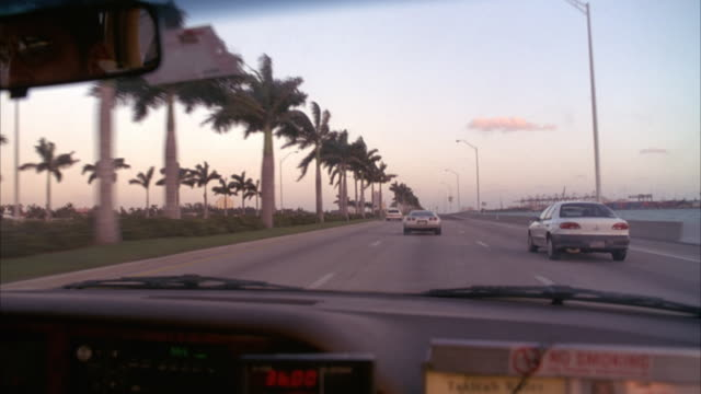 vídeos de stock, filmes e b-roll de medium angle driving pov from passenger seat of possible taxi. see cars driving on three lane highway ahead of pov. see palm trees growing on median. - 1990 1999