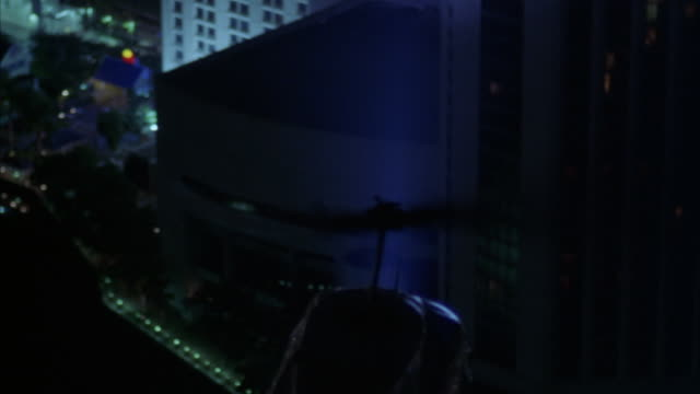 """aerial of helicopter flying above downtown miami at night. see """"metro police"""" and """"police"""" signs on side of helicopter. - suchscheinwerfer stock-videos und b-roll-filmmaterial"""