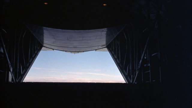 medium angle of cargo airplane rear hatch doors opening during flight. see loading platform descend into position.  see clouds and blue sky. see part of airplane tail. - airplane part stock videos and b-roll footage