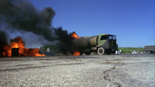 vídeos de stock e filmes b-roll de wide angle of camouflaged painted military tanker truck burning and exploding. see possible fuel station burning at frame left. - grade de radiador