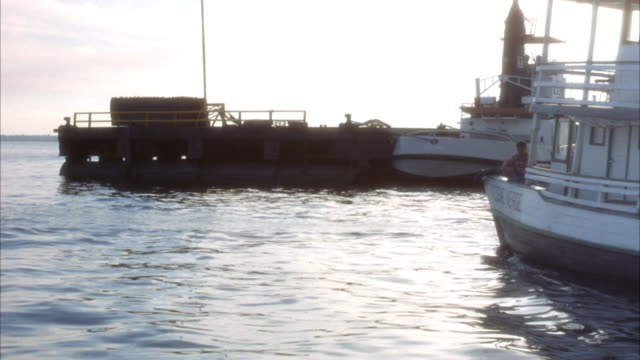 stockvideo's en b-roll-footage met medium angle pan left of small three-decked ferry sailing out to sea. see docks with anchored fishing boats. see skiff with motor travel from frame left to right. - anchored