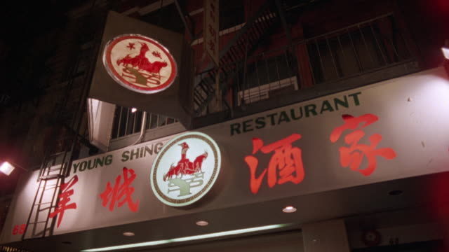 "vídeos de stock, filmes e b-roll de medium angle of sign of chinese restaurant with chinese characters and dragon logo. ""young shing restaurant"" written above characters on sign. - língua chinesa"