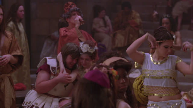 medium angle of women belly dancing, men, women, people wearing robes and togas drinking, talking at gathering or party. could be in ancient rome. - stile classico romano video stock e b–roll