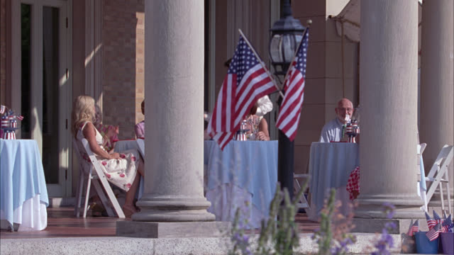 wide angle of outdoor patio at upper class hotel or country club. people dine outside. american flag decorations. could be fourth of july. pillars or columns on patio. - clubhouse stock videos & royalty-free footage
