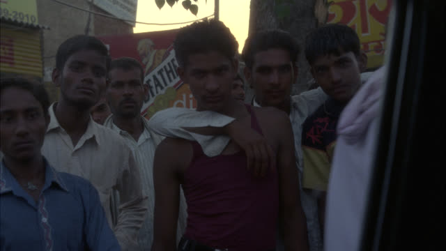 MEDIUM ANGLE POV OF MEN STANDING ON STREET IN LOWER CLASS RURAL AREA. COULD BE SLUM. BUSINESSES WITH SIGNS WRITTEN IN HINDI. MEN STARE AT WINDOWS OF CAR. COULD BE MARKETPLACE IN POOR, RURAL VILLAGE. FRUIT STANDS OR VENDORS VISIBLE. BICYCLES.