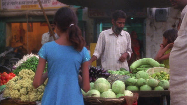 MEDIUM ANGLE OF STREET VENDOR SELLING FRUITS AND VEGETABLES. PRODUCE STAND. COULD BE IN MARKETPLACE. LOWER CLASS TOWN.