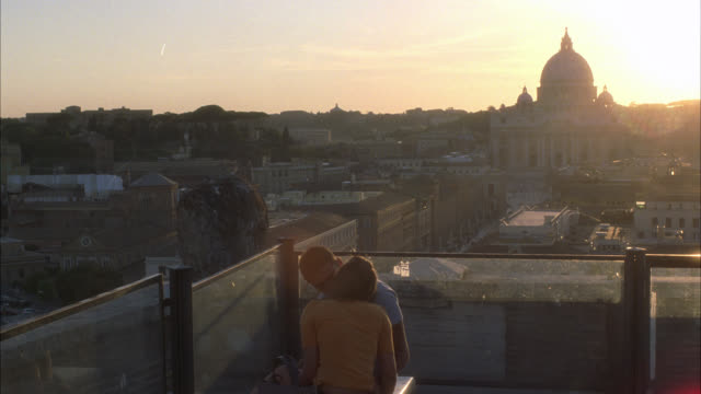 wide angle of vatican city skyline. st. peter's basilica in the bg. church or cathedral. domed building. multi-story apartment buildings. sunset. two people kissing in fg. could be on rooftop. religious, catholic. - building storey stock videos and b-roll footage