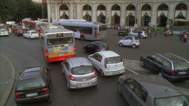 high angle down driving pov of piazza della repubblica, roundabout or traffic circle. cars and buses driving on city streets. could be pov from double-decker bus. traffic jam. europe. - rom stock-videos und b-roll-filmmaterial