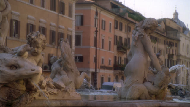 close angle of sculptures or statues in fountain of neptune in piazza navona. plaza or town square. fountain of the four rivers in bg. multi-story middle class apartment buildings. - middle class stock videos & royalty-free footage