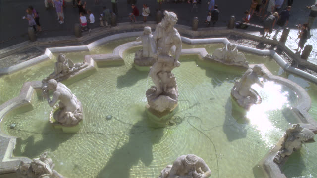 pan down to stone sculptures or statues in the moor fountain in piazza navona. people, pedestrians, tourists. multi-story middle class apartment buildings in bg. plaza or town square. - middle class stock videos & royalty-free footage