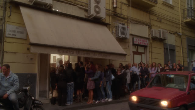 """wide angle of people standing in line outside of pizzeria in italy. city streets. pedestrians and people on motorcycles. restaurants. awning over doorway reads """"cantica pizzeria da michele."""" - awning stock videos & royalty-free footage"""