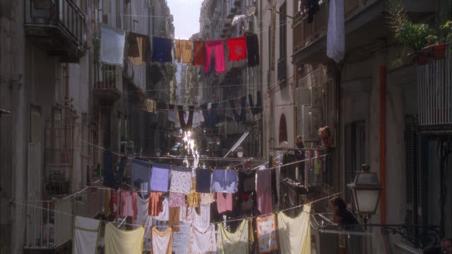 pan up of laundry on clotheslines across city street or alley in italy. people or pedestrians walking. could be naples. apartment buildings and balconies. people. - vicolo video stock e b–roll