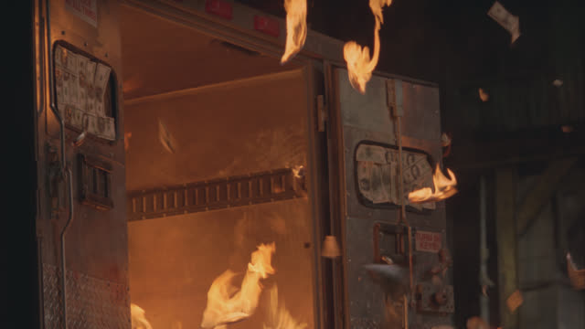 medium angle of a man being thrown back from an armored truck exploding. flames, smoke, fire erupts from back of vehicle. man suffering from being burned seen trying to exit vehicle. american currency flies out of truck during explosion. - armored truck stock videos and b-roll footage