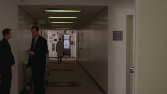 WIDE ANGLE OF TWO MEN IN SUITS CHATTING IN HALLWAY OF HOSPITAL OR MEDICAL CENTER. DOORWAYS TO HOSPITAL ROOMS VISIBLE. DOCTORS IN WHITE LAB COATS WALK BY IN BG.