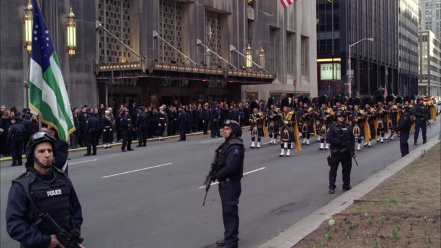 WIDE ANGLE OF PARADE OR MILITARY FUNERAL PROCESSION WITH ARMED POLICE OFFICERS CONTROLLING CROWD ON SIDEWALK AS BAGPIPERS MARCH DOWN STREET. FLAGS. WALDORF ASTORIA HOTEL IN BG.