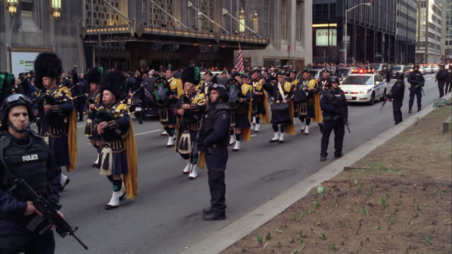 WIDE ANGLE OF PARADE OR MILITARY FUNERAL PROCESSION WITH ARMED POLICE OFFICERS CONTROLLING CROWD ON SIDEWALK AS BAGPIPERS MARCH DOWN STREET. FLAGS. WALDORF ASTORIA HOTEL IN BG. POLICE CARS WITH FLASHING LIGHTS OR BIZBAR FOLLOW.