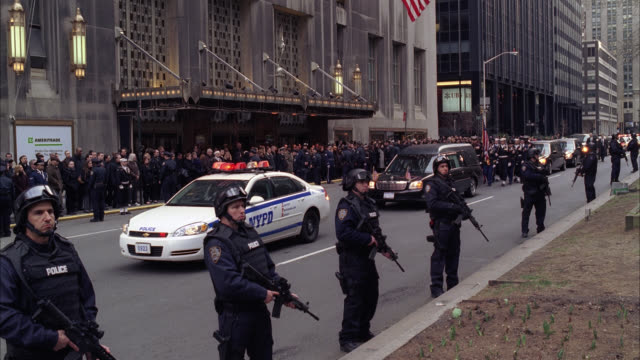 WIDE ANGLE OF PARADE OR MILITARY FUNERAL PROCESSION WITH ARMED POLICE OFFICERS CONTROLLING CROWD ON SIDEWALK. SOLDIERS MARCH NEXT TO HEARSE. WALDORF ASTORIA HOTEL IN BG. POLICE CARS WITH FLASHING LIGHTS OR BIZBAR FOLLOW. LIMOUSINES.