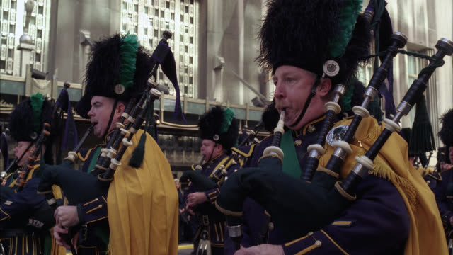 close angle of bagpipers and drummers hitting snare drums during parade or funeral procession. men dressed in bagpiper uniforms. city streets. emerald society band. irish police officer society. office buildings visible in bg. crowds on sidewalk in bg. ma - ウォルドルフ・アストリア点の映像素材/bロール