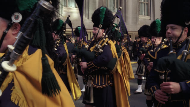 medium angle of bagpipers marching in parade or funeral procession. men dressed in bagpiper uniforms. city streets. emerald society band. irish police officer society. office buildings visible in bg. crowds on sidewalk in bg. marching bands. waldorf astor - ウォルドルフ・アストリア点の映像素材/bロール
