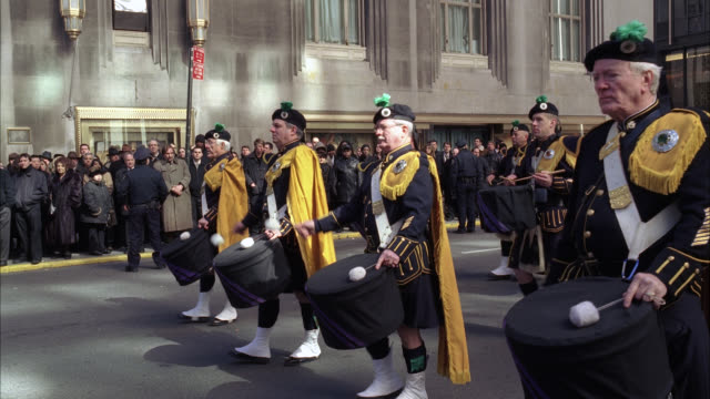 medium angle of bagpiper drummers marching in parade or funeral procession. men dressed in bagpiper uniforms hitting bass and snare drums. city streets. emerald society band. irish police officer society. office buildings visible in bg. crowds on sidewalk - ウォルドルフ・アストリア点の映像素材/bロール