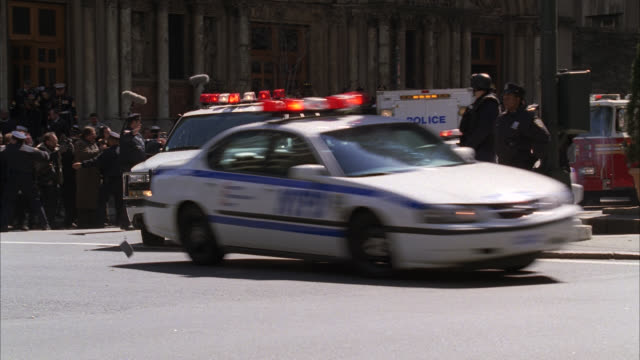 MEDIUM ANGLE OF STREET CORNER IN NEW YORK WITH POLICE CARS, AMBULANCES, AND FIRE TRUCKS. COULD BE EVACUATION OR EMERGENCY. POLICE CAR AND SUV WITH FLASHING LIGHTS OR BIZBAR SPEED AROUND CORNER AND DRIVE AWAY. ARMED POLICE OFFICERS STAND ON STREET.