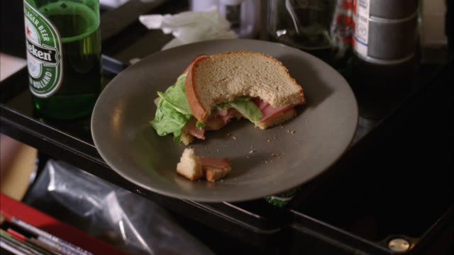 zoom in close angle of heineken beer bottle and half eaten sandwich on desk. file folders visible in drawer. camera zooms in and out. could be lunch or snack. - sandwich stock videos & royalty-free footage